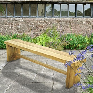 The Forest Double Sleeper Wooden Garden Bench 6x1, positioned on grass at the side of a path, with yellow and orange flowers in the background.