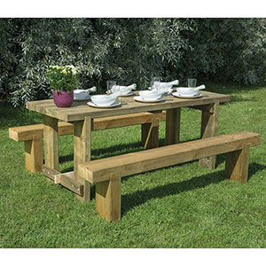 The Forest Sleeper Bench and Refectory Wooden Garden Table Set, with crockery on the table, and positioned on a lawn.