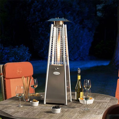 A small outdoor heater on a wooden table, next to some wine glasses