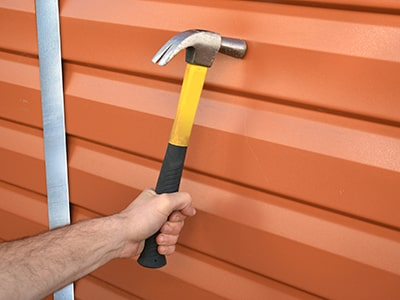 plastic shed panel being hit by a hammer as strength test