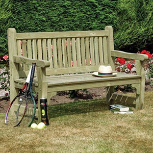 The Rowlinson Softwood Wooden Garden Bench, hat on the seat, tennis rackets to the side, book underneath and situated on a lawn.