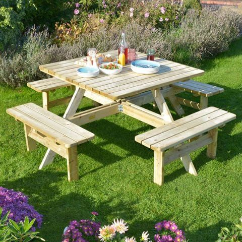 The Rowlinson Square Wooden Garden Picnic Table, nibbles and condiments on the table, which is situated on a lawn.