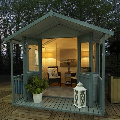 a shed with a veranda, furnished with chairs and solar lighting