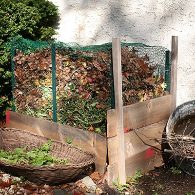 a square, wooden compost bin with green mesh sides
