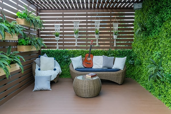 a secluded garden deck with slatted panel and lots of plants