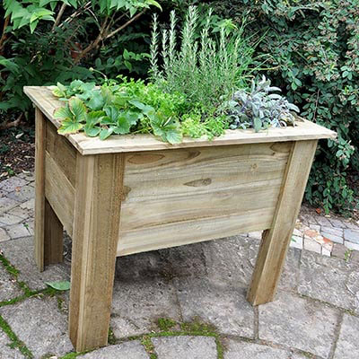 A 3x2 wooden garden planter, containing plants and herbs