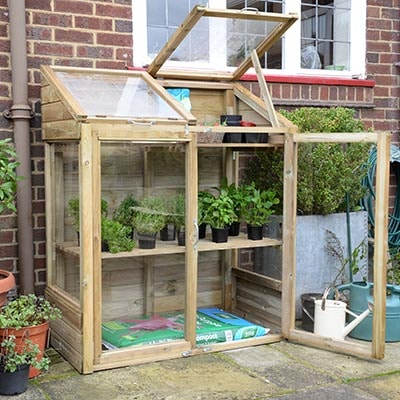 a small wooden-framed greenhouse, positioned against a wall