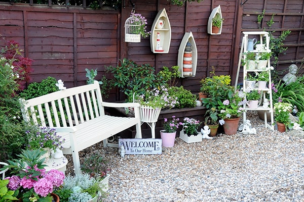a garden bench next to a fence with lots of decorative accessories