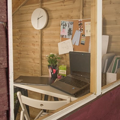 the view into a garden shed window to see a home office