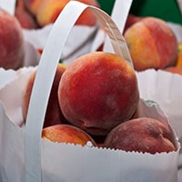 Lots of ripe peaches in white paper bags.