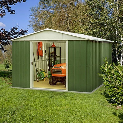 A large, green, metal shed, doors open to reveal a ride-on mower