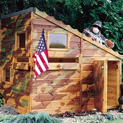 a wooden playhouse, painted in camouflage colours, with 2 windows, an open door and displaying an American flag
