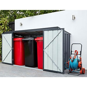 The 7x3 Lotus Anthracite Grey Metal Triple Bins Store, situated on a patio, with doors open and 3 wheelie bins inside.