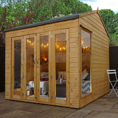 A wooden summer house with 12mm tongue and groove cladding, as well as bi-fold doors