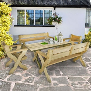 The Forest Grizedale 8 Seater Wooden Garden Table and Chairs Dining Set, situated outside a white, thatched cottage.