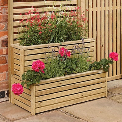 A 2-tiered wooden planter with deep pink flowers inside