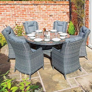 A grey garden furniture set, including 6 rattan dining chairs and a round, glass-top table, all situated on a patio.
