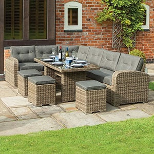 A grey rattan garden table and chairs corner dining set, table laid, situated on a patio.