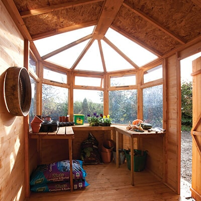 the inside of a potting shed, including potting benches and plants