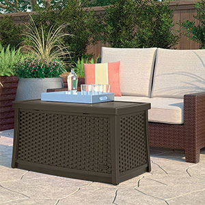 A drinks tray resting on top of the Suncast Elements Plastic Garden Coffee Table (with Storage), which is situated on a patio, next to a garden sofa.