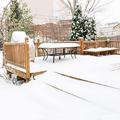 outdoor furniture on garden decking, all covered in snow