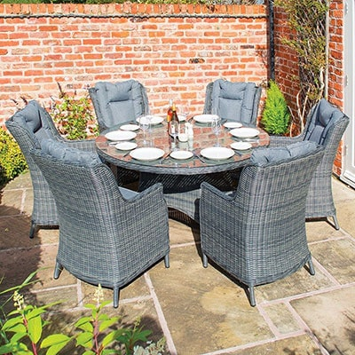 A grey rattan dining set, consisting of 6 chairs and a round glass-top table.
